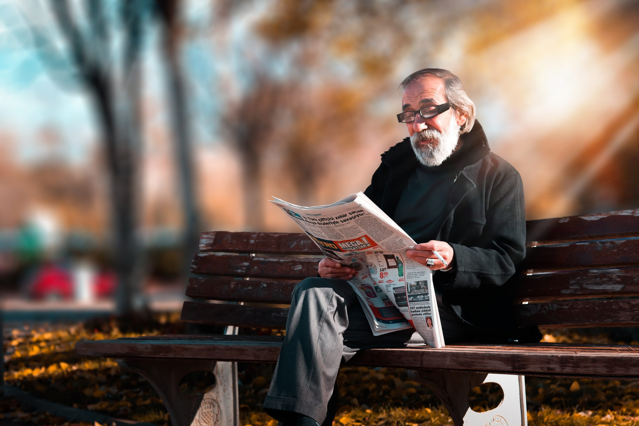 old man reading newspaper on bench